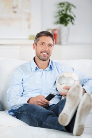 feet relaxing: Mature man with soccer ball and remote control watching soccer on tv at home