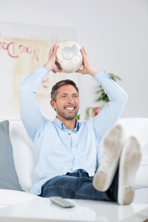 pies masculinos: Feliz el hombre maduro con balón de fútbol viendo el partido de fútbol en casa