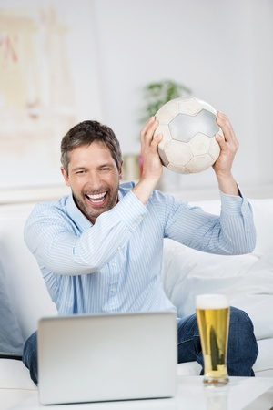 Happy mature man with soccer ball and beer watching soccer match on laptop at home