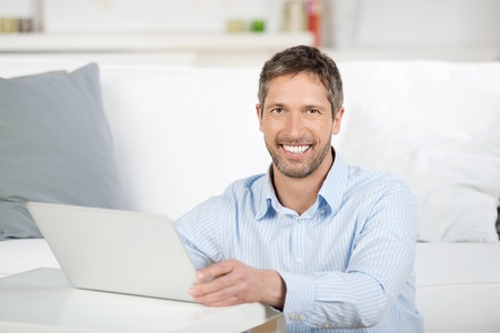 Portrait of happy mature man with laptop in house photo