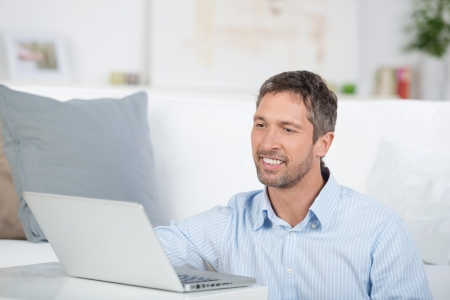 Portrait of happy smiling mature man with laptop in house photo