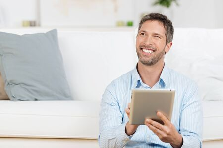 Portrait of happy mature man holding laptop while looking away in house photo