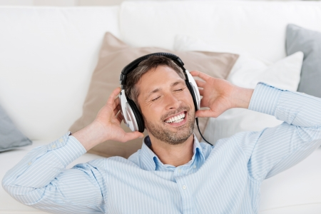 leisureliness: Handsome mature man with eyes closed enjoying music on headphones while leaning on sofa at home