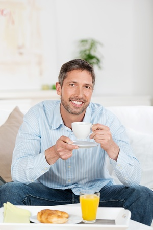 Portrait of happy mature man having breakfast on sofa at home photo