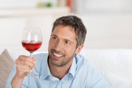 connaisseur: Ritratto di uomo maturo, guardando il bicchiere di vino a casa Archivio Fotografico