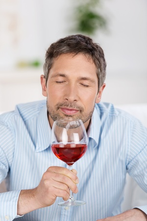 wine testing: Portrait of happy mature man testing wine at home Stock Photo