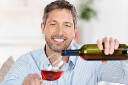 mid adult men: Happy mature man pouring wine in wineglass at home