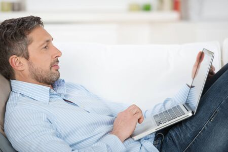 Side view of happy mature man holding laptop while lying on couch in house photo