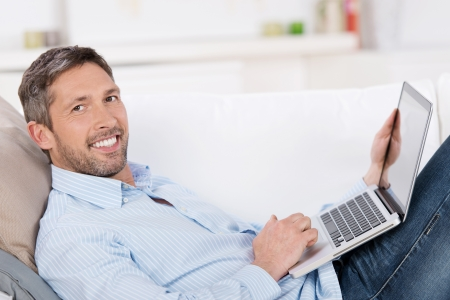 guy with laptop: Portrait of happy mature man holding laptop while lying on sofa in house