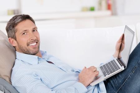 Retrato de hombre maduro feliz celebración portátil mientras está acostado en el sofá en casa Foto de archivo - 21112028