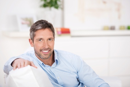 mid adult men: Portrait of mature man sitting on sofa at home Stock Photo