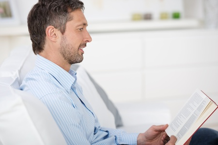 leisureliness: Side view of mature man reading book while sitting on sofa at home Stock Photo