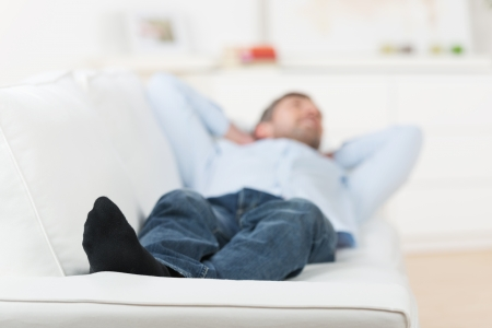 unwinding: Mature man with hands behind head lying on couch at home