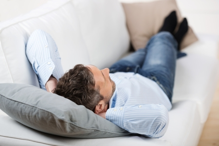 leisureliness: Rear view on mature man with hands behind head lying on sofa at home Stock Photo
