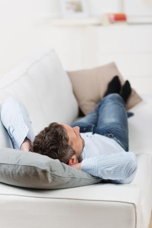 손을 머리 뒤에 집에서 소파에 누워 성숙한 남자의 후면보기 스톡 콘텐츠