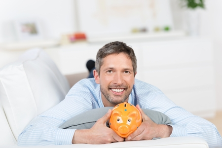 leisureliness: Portrait of mature man holding piggybank while lying on sofa at home