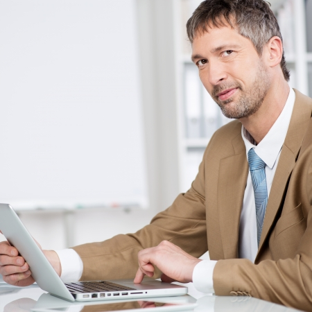 mature businessman: Portrait of mature businessman with laptop smiling at desk in office