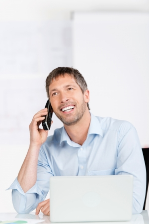 Happy mature businessman with laptop using cordless phone at office desk photo