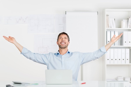 Happy successful businessman with arms raised sitting at office desk photo