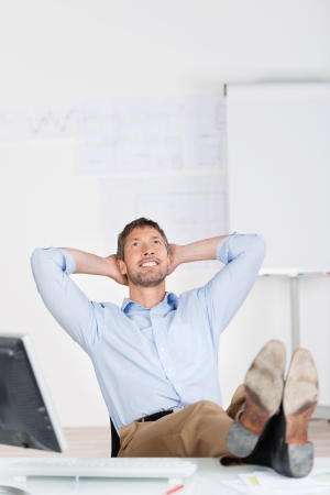 Happy thoughtful businessman with hands behind head looking up at office desk photo