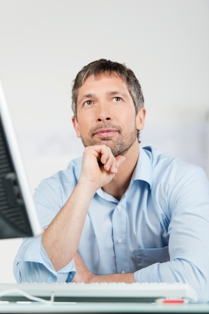 shirtsleeves: Portrait of thoughtful businessman with computer at desk in office