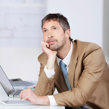 Portrait of thoughtful businessman with hand on chin at desk in office photo