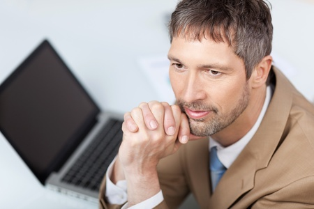 High angle view of thoughtful businessman with laptop at desk in office photo