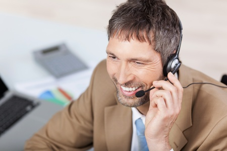 Mature male customer service executive conversing on headset at desk in office photo