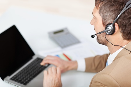 Rear view of mature male customer service executive conversing on headset at desk in office photo