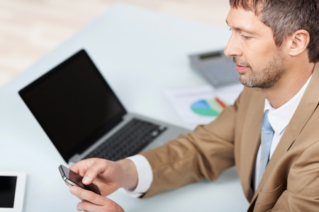 high angles: High angle view of mature businessman using mobile phone at desk in office