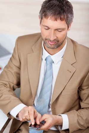 High angle view of smiling mature businessman using mobile phone in office Stock fotó