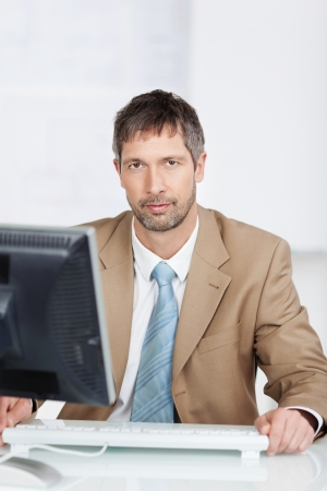 Portrait of serious mature businessman with computer screen at office desk Stock Photo - 21112141