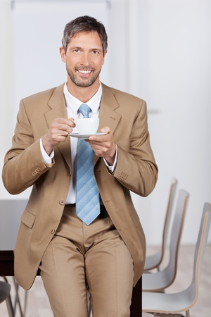 Mature smiling businessman having coffee while leaning on desk in office photo