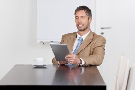 mature businessman: Mature businessman using digital tablet at desk in office