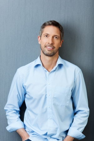 one mid adult male: Portrait mature businessman smiling while standing against blue wall
