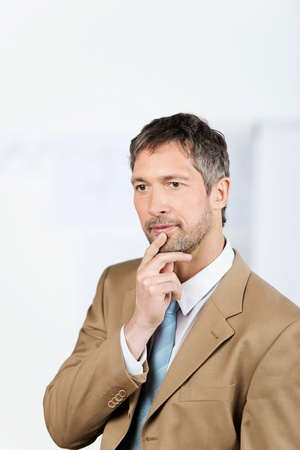 hand on chin: Thoughtful mature businessman with hand on chin looking away in office Stock Photo