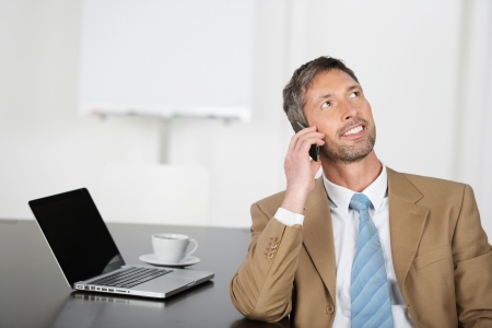 mature businessman: Mature businessman using mobile phone while looking up at office desk Stock Photo