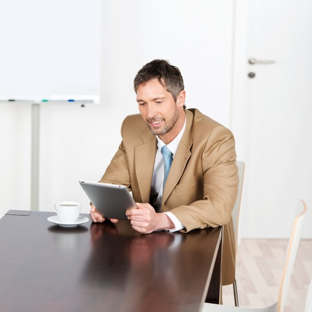 Mature businessman using digital tablet while sitting on desk in office photo