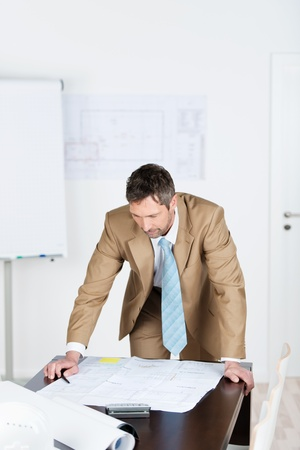 Portrait of mature male architect working on blue print at desk in office photo