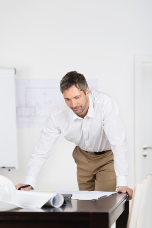 Mature male architect looking at blueprint at desk in office photo