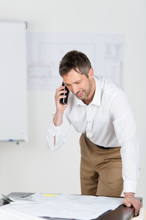 Mature male architect looking at blueprint while using cordless phone at desk in office photo