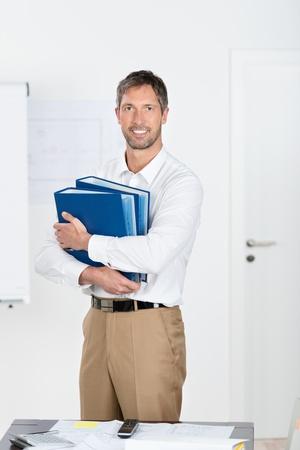 mature businessman: Portrait of smiling mature businessman holding binders in office