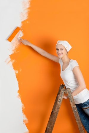 Portrait of happy young woman painting wall with roller in house photo
