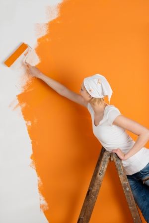 woman standing on ladder and painting wall in orange photo