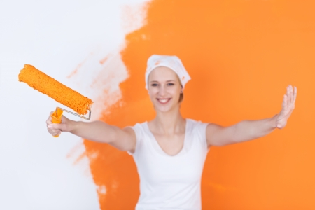 happy woman painting house with orange color photo