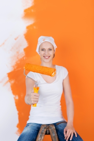 smiling woman sitting on ladder and renovating flat photo