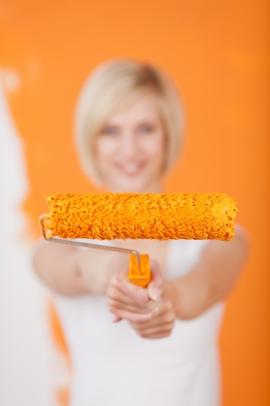 happy woman showing paint roller against orange painted wall photo