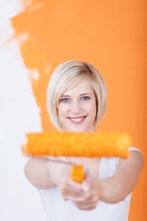 Portrait of happy young woman holding paint roller against half painted wall photo