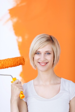 young woman painting a wall in orange color photo