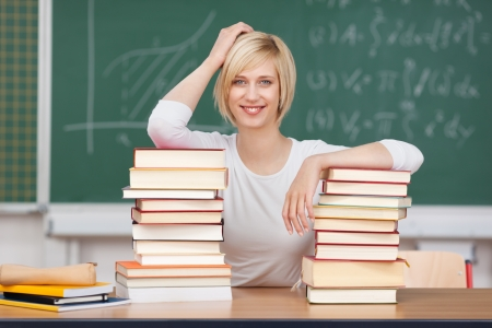 woman with stacked books in front of board in classroom photo